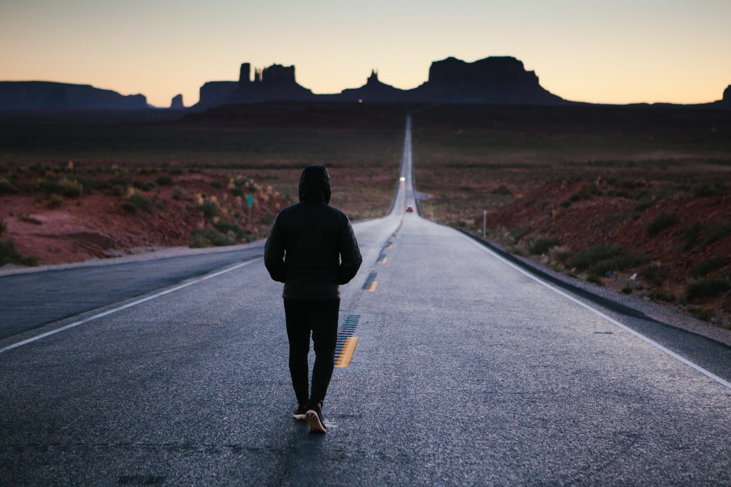 person walking in the center of the road